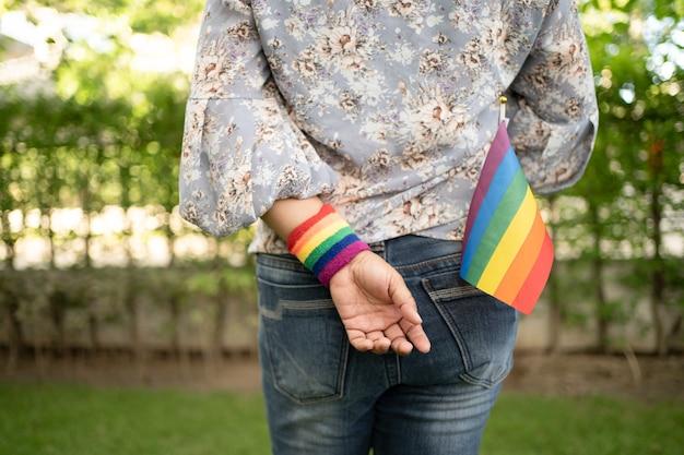 Lgbtプライド月間の虹色の旗のシンボルを保持しているアジアの女性