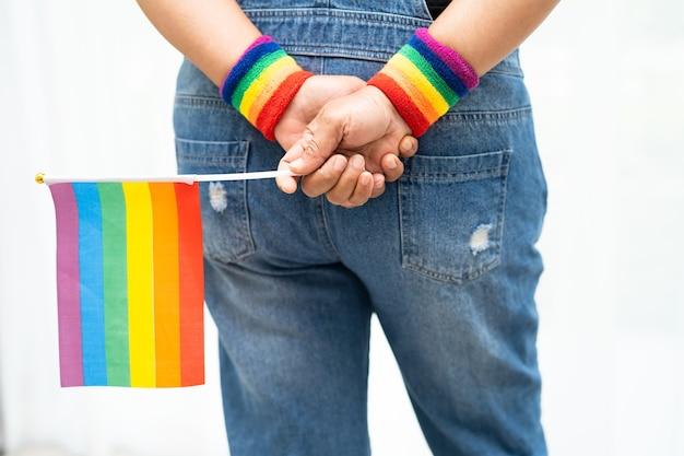 Lgbtプライド月の虹色の旗のシンボルを保持しているアジアの女性