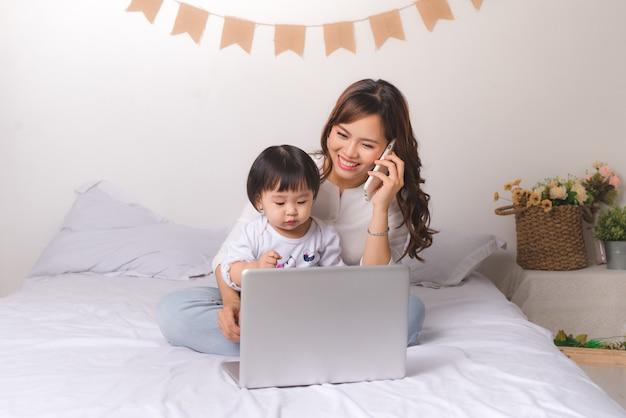 고전적인 양복을 입은 아시아 여성이 휴대전화로 통화하고 집에서 딸과 함께 노트북 작업을 하고 있습니다.
