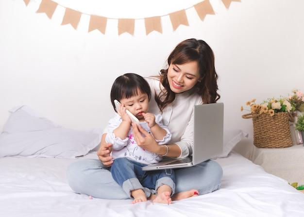 집에서 노트북 작업을 하는 클래식 슈트를 입은 아시아 여성이 아버지와 수다를 떨고 있습니다.