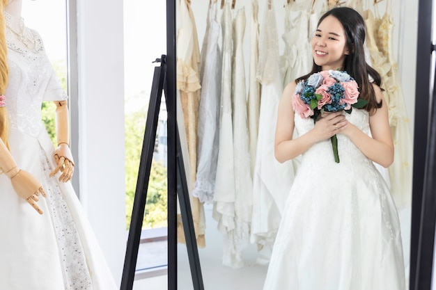 Asian lady is looking into the mirror and smiling while choosing wedding dresses in shop.