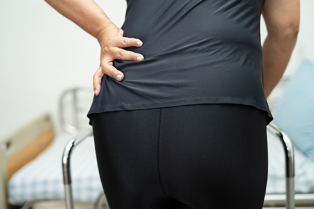 アジアの女性患者は、歩行器で背中、腰、整形外科の腰を痛めています。