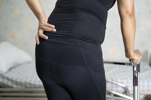 워커와 정형 외과 요추에 대한 허리 통증 지원 벨트를 착용하는 아시아 여자 환자.