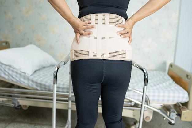 Азиатская женщина-пациентка носит пояс для поддержки боли в спине для ортопедического поясничного отдела с ходунками.