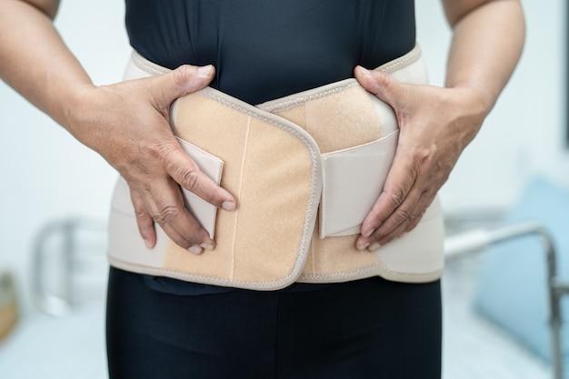 整形外科腰椎用の腰痛サポートベルトを着用しているアジアの女性患者。
