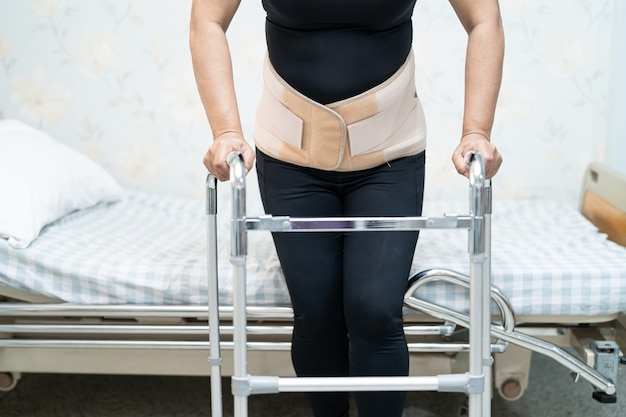 Asian lady patient wearing back pain support belt for orthopedic lumbar with walker
