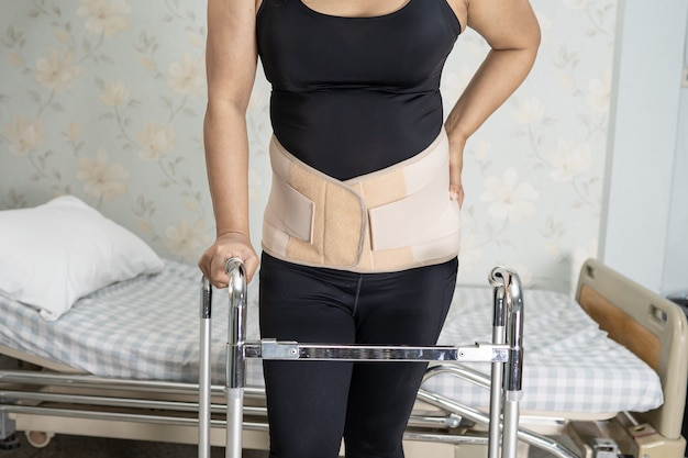 Asian lady patient wearing back pain support belt with walker