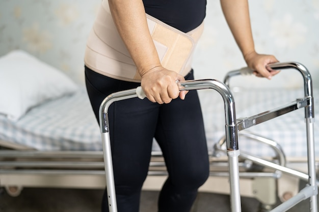 Asian lady patient wearing back pain support belt.