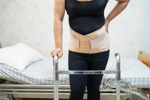 허리 통증 지원 벨트를 착용하는 아시아 여자 환자.