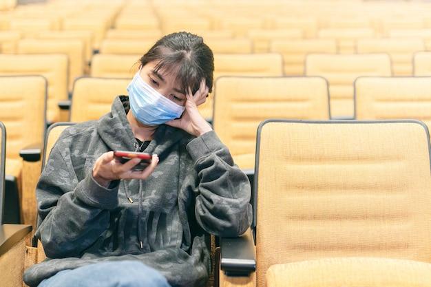 Азиатская дама, защищая себя от вируса, носить защитную маску с помощью смартфона.