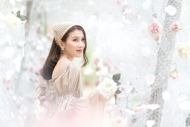 Азиатская дама улыбается и стоит в цветочном саду белых роз, как естественная, роскошная тема