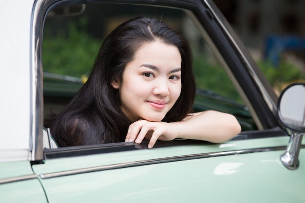 Asian lady smiling in a vintage car