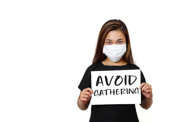 Asian lady standing with avoid gathering text front view in white plain wall young lady looking straight wearing face mask for health and safety to avoid coronavirus
