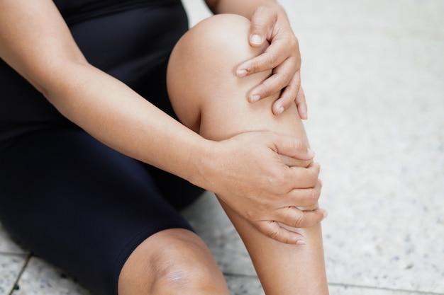 Азиатская дама касается и чувствует боль в колене и ноге