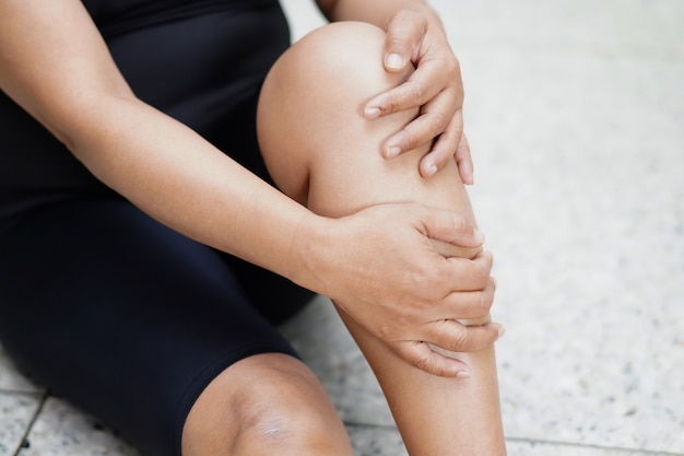 Asian lady touches and feels pain in her knee and leg