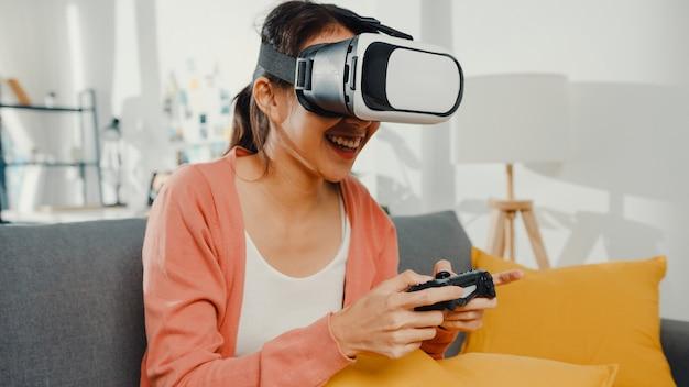アジアの女性が仮想現実のヘッドセットメガネを着用して家のリビングルームのソファでジョイスティックゲームをプレイ
