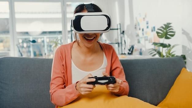 Signora asiatica indossa occhiali auricolare di realtà virtuale gioca a joystick sul divano nel soggiorno di casa