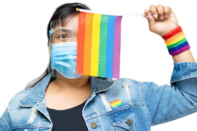 虹色の旗、lgbtプライド月のシンボルを保持しているブルージーンズのジャケットを着ているアジアの女性。