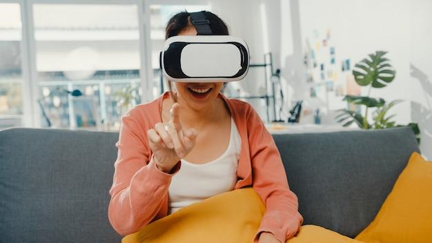 家の居間でソファに座って手をジェスチャーするバーチャルリアリティのヘッドセット眼鏡をかけているアジアの女性。