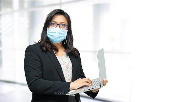 安全感染covid-19コロナウイルスを保護するためにオフィスで新しい通常のマスクを身に着けているアジアの女性。