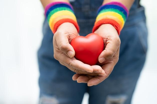 무지개 깃발 팔찌를 착용하고 붉은 심장을 들고 있는 아시아 여성은 lgbt 프라이드의 달의 상징인 동성애자, 레즈비언, 양성애자, 트랜스젠더, 인권의 6월 사회를 축하합니다.
