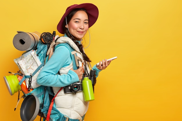 Asian lady with pleased expression, tries to find route with online navigation map, holds mobile phone, wears hat, casual clothes, carries rucksack, flask, binoculars, isolated on yellow wall