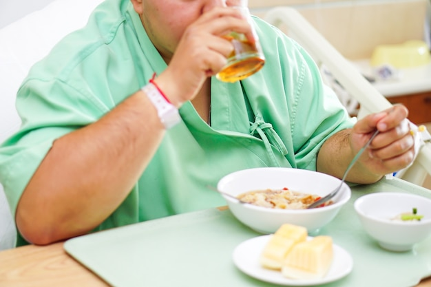 アジア女性の女性患者病院で朝食健康的な食べ物を食べる。