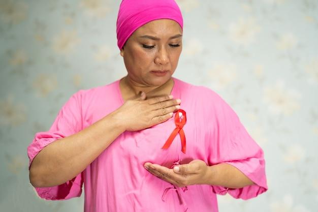 アジアの女性女性患者の痛みと病院での彼女の胸の心配、世界乳がんの日の象徴。