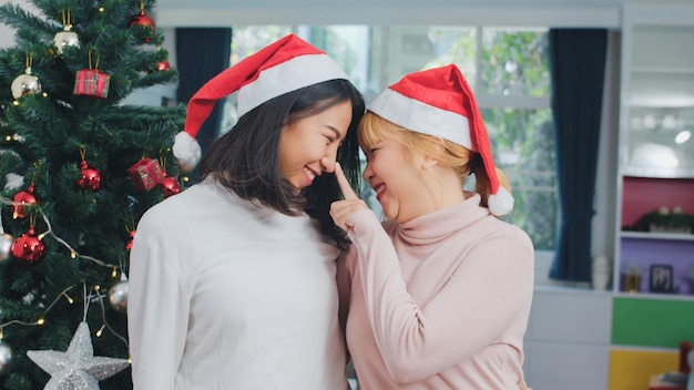 Asian lesbian couple celebrate christmas festival. lgbtq female teen wear christmas hat relax happy smiling looking enjoy xmas winter holidays together in living room at home.
