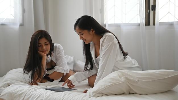Азиатская лесбийская пара лгбт использует планшет и проводит время вместе