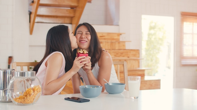Asian lesbian lgbtq women couple giving present home