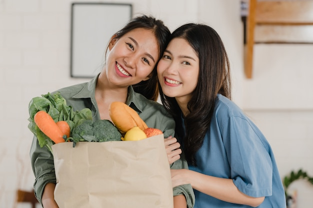 Asian lesbian lgbtq women couple hold grocery shopping paper bags at home