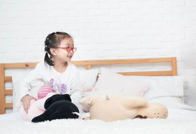 Asian little adorable girl sit in bed among many toys