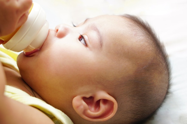 An asian little baby drinking milk from bottle on bed the concept of empathy adorable and pretty