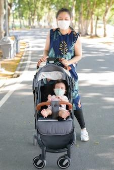庭でマスクを身に着けている母親と一緒にベビーカーに座っているフェイスマスクを持つアジアの小さな女の赤ちゃん