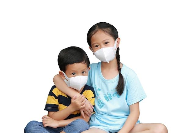 아시아의 어린 소년과 소녀는 위생 마스크를 함께 쓰고 흰색 배경에 격리된 카메라를 보고 있습니다. 클리핑 패스가 있는 이미지