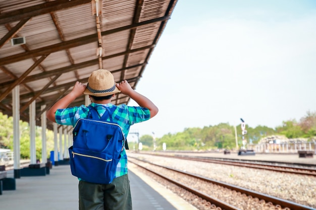 Asian little boy carrying a blue backpack standing waiting for the train to go to school