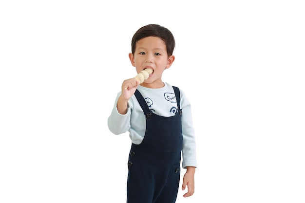 Asian little boy eating meat ball stick isolated on white background. portrait of caucasian kid holding meatball with looking at camera with clipping path
