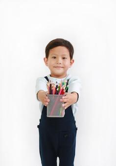 흰색 배경에 대해 색연필 바구니를 주는 아시아 소년. 그의 손에 있는 색연필에 초점