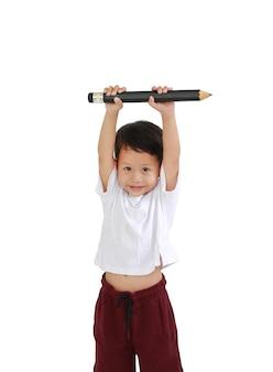 アジアの少年は、白い背景で隔離の頭の上に大きな鉛筆を保持し、持ち上げます。子供と教育のコンセプト