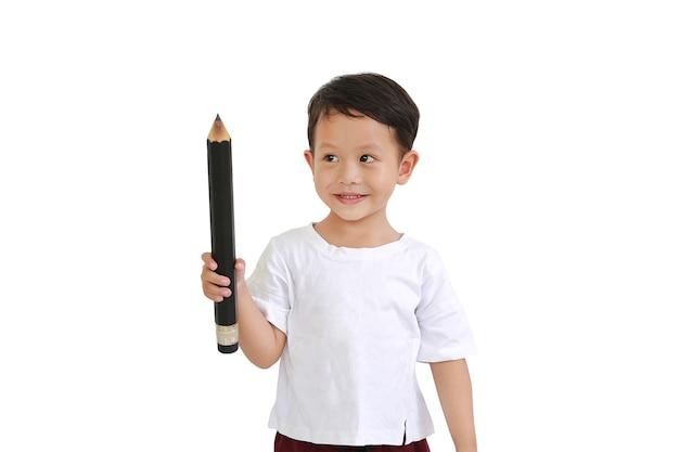 大きな鉛筆を持って、白い背景で隔離を見上げるアジアの少年。子供と教育のコンセプト
