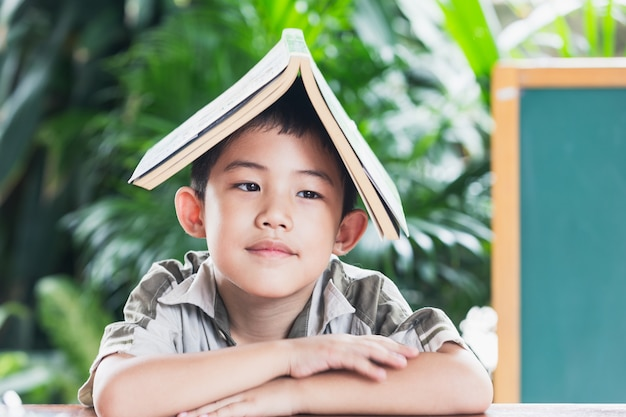 Asian little boy holding book on head education concept