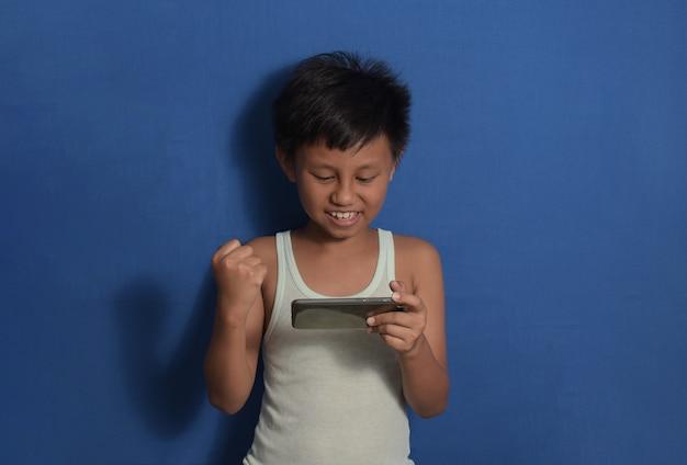 携帯電話でゲームをしている青い背景の上に孤立して立っているアンダーシャツのアジアの小さな男の子
