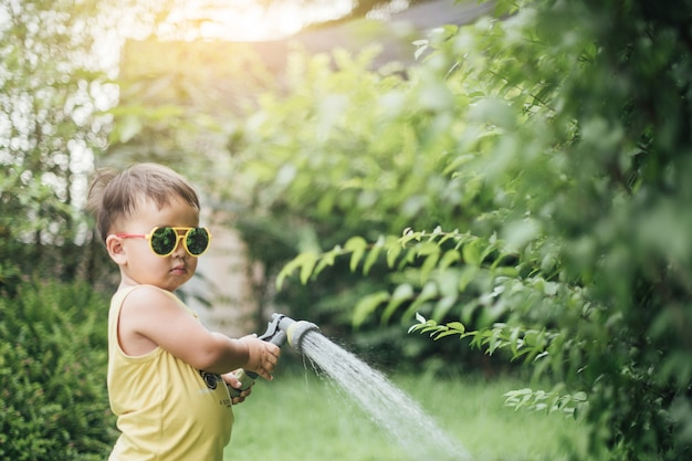 Asian little boy pouring water on the trees.kid helps to care for the plants with a watering can in the garden.