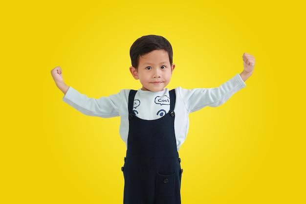 黄色の背景に分離された強いジェスチャーのために手を上げるアジアの小さな男の子。クリッピングパスのある画像