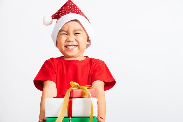 赤いサンタに身を包んだアジアの小さな男の子の笑顔と興奮は、手にギフトボックスを保持します