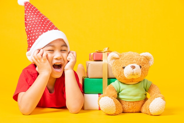 赤いサンタのアジアの小さな男の子の笑顔の休日のクリスマスの概念
