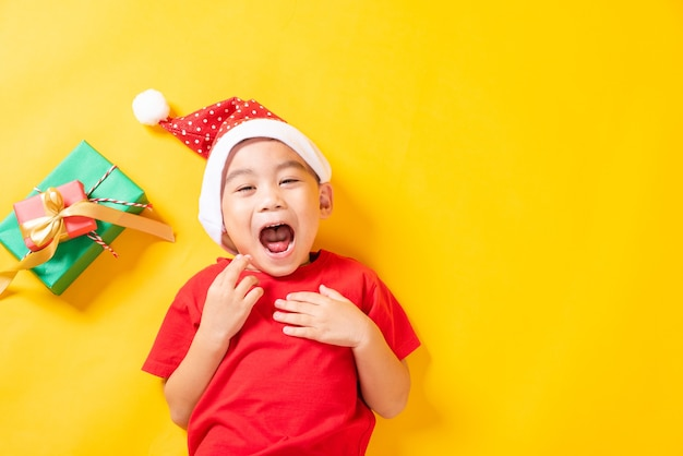 Asian little boy smile in red santa claus hat