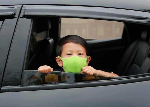 衛生コロナウイルス(covid-19)の発生時に、衛生フェイスマスクを着用したアジアの少年が車の窓から頭を突く