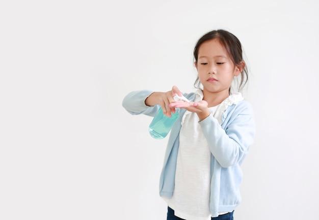 衛生のための手の洗浄にプラスチックボトルからアルコールゲルを適用するアジアの小さな子供